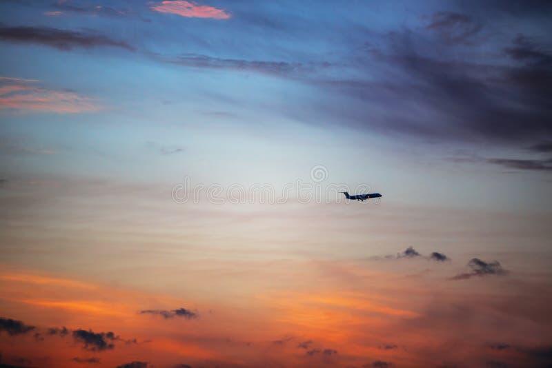 Dramatiskt himmelmoln och flygplan för solnedgång fotografering för bildbyråer