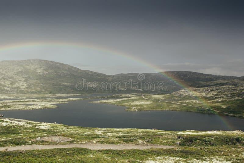 Dramatiskt landskap med den härliga regnbågen över arktiska ängar, berget och sjön arkivfoto