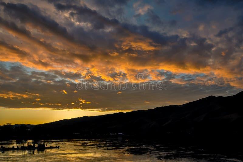 Dramatiskt solnedgånglandskap med sjön, himmelreflexion, fiskebåten och utlöparekonturn Snake River på gränsen av Idaho och royaltyfri bild