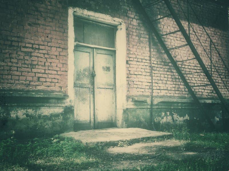 Dramatiskt tappningfoto av en gammal övergiven herrgård Hus med sp?karna royaltyfria foton