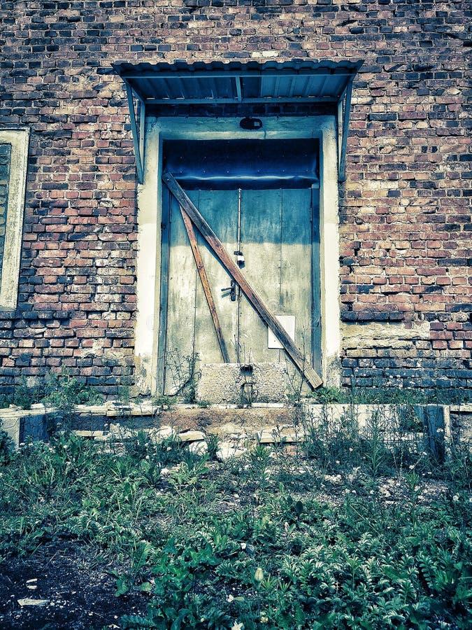 Dramatiskt tappningfoto av en gammal övergiven herrgård Hus med sp?karna arkivfoto