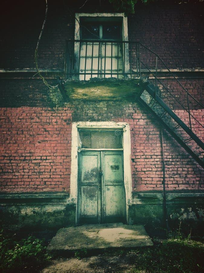Dramatiskt tappningfoto av en gammal övergiven herrgård Hus med sp?karna royaltyfria bilder