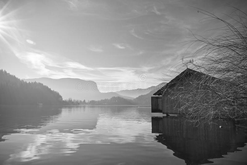 Dramatyczna sylwetka drewniany boathouse na czystym jeziorze krwawił w bezpośrednim świetle słonecznym i odbiciu w wodzie w zimie obrazy stock