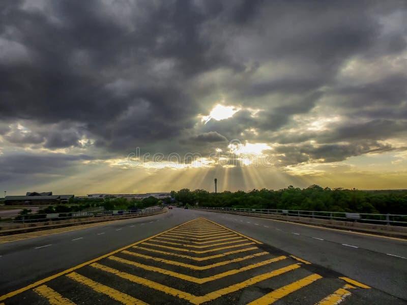 Dramatyczne burzowe chmury nad rozdroża z promieniami światła słonecznego jaśnienie obrazy royalty free