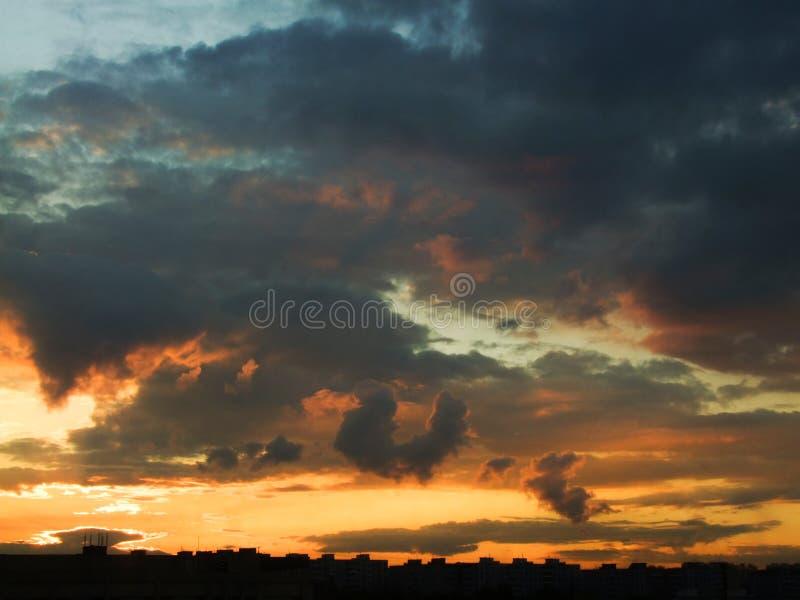 Dramatyczne chmury nad miastem piękny zachód słońca zdjęcie stock