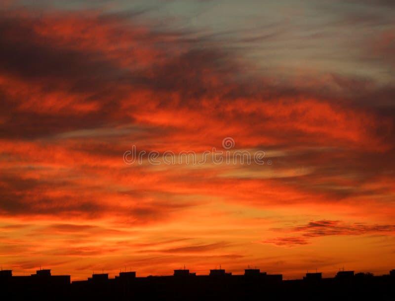 Dramatyczne chmury nad miastem piękny zachód słońca obraz royalty free