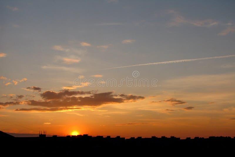 Dramatyczne chmury nad miastem piękny zachód słońca zdjęcia royalty free