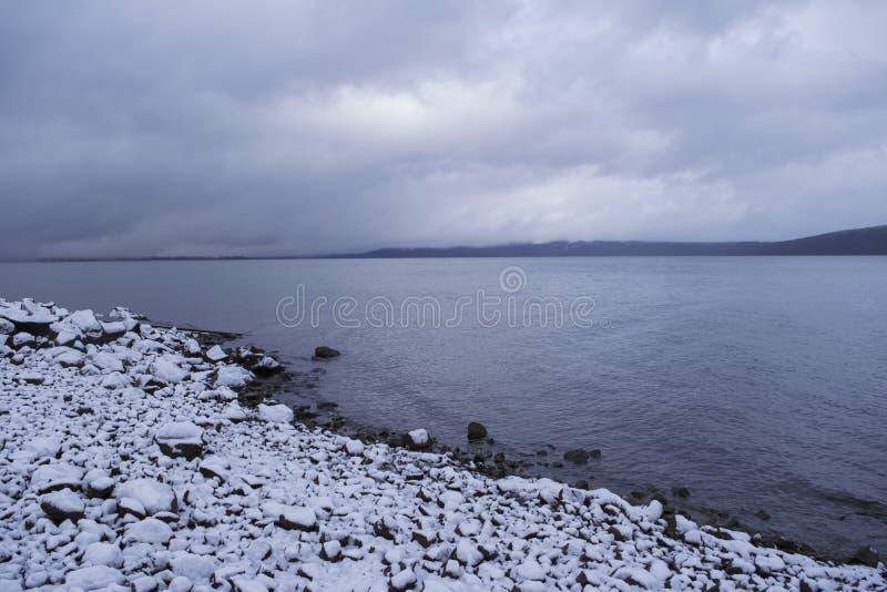 Dramatyczne chmury nad zimy jeziorną sceną z śnieżnym brzeg zdjęcia stock