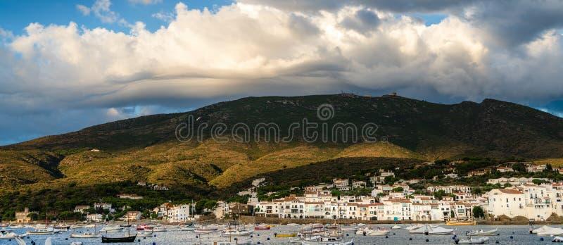 Dramatyczne chmury tworzą nad wzgórzami nad zatoki i nadmorski miasteczko Cadaques, Girona, Catalonia, Hiszpania Łodzie cumować n obrazy royalty free