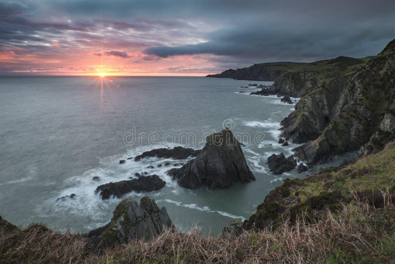 Dramatyczny burzowy wschodu słońca krajobraz nad byka punktem w Devon Engla fotografia stock