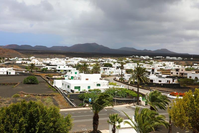 Dramatyczny chmury niebo na Yaiza wiosce z białymi małymi drzewkami palmowymi w Lanzarote wyspach i domami, Hiszpania obrazy royalty free