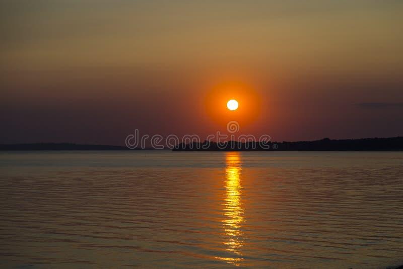 Dramatyczny czerwony zmierzch nad spokojnym jeziorem fotografia royalty free