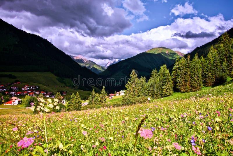 Dramatyczny niebo po tym jak burza pod zmrokiem - błękitny złowrogi niebo z wysokogórskimi szczytami w Berwang, Tirol zdjęcie stock
