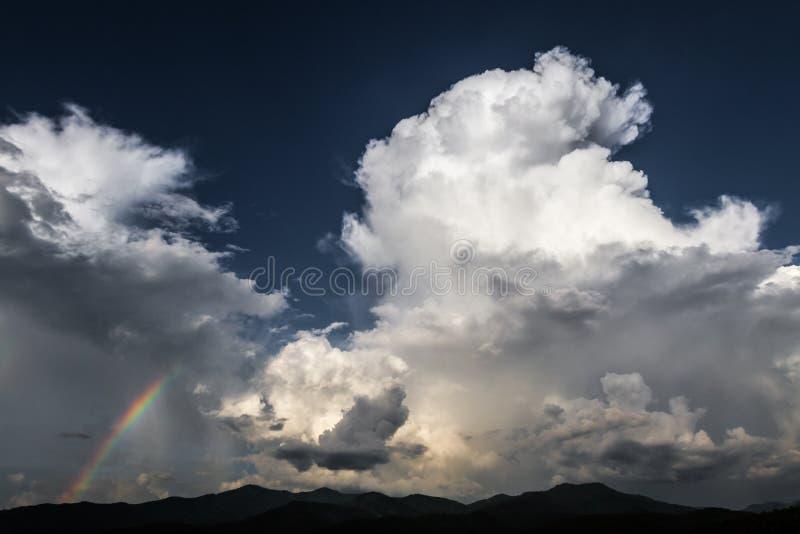 Dramatyczny niebo z ogromną ciemną biel obłoczną i zadziwiającą tęczą zdjęcia stock
