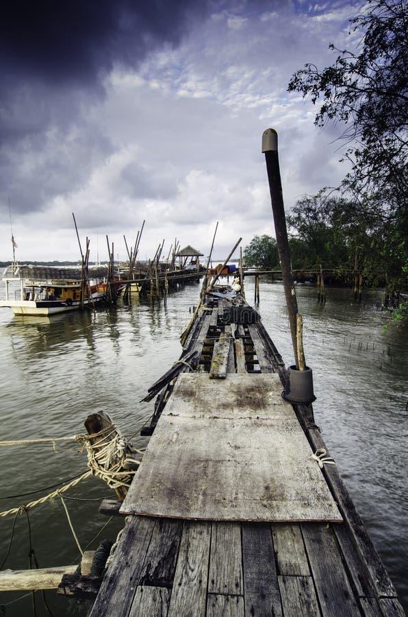 Dramatyczny ranek z zmrokiem chmurnieje przy drewnianym jetty obrazy stock