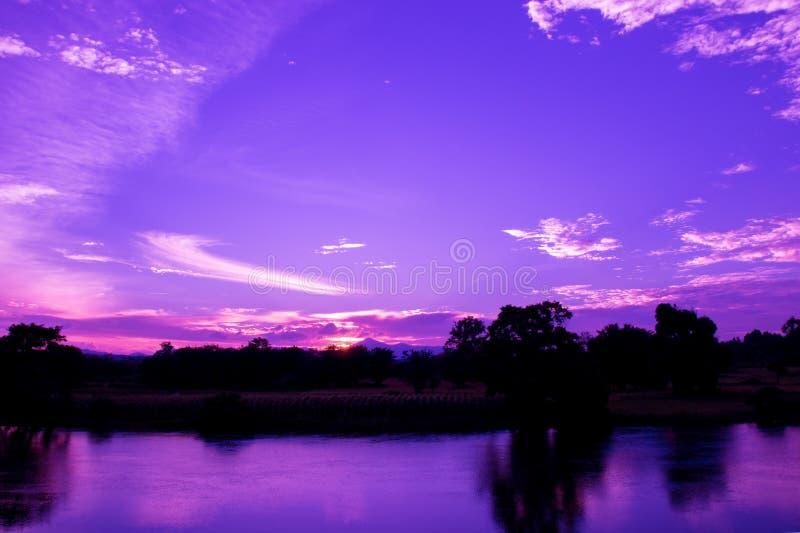 Dramatyczny zmierzch w niebie i odbija rzecznego pięknego kolorowego brzmienie purpur krajobrazu sylwetki błękitnego drzewnego la zdjęcie royalty free