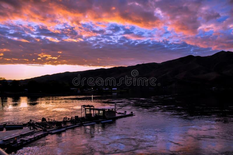 Dramatyczny zmierzchu krajobraz z jeziorem, nieba odbiciem, łodzią i pogórze sylwetką, Wi się rzekę na granicie Idaho i domycie fotografia stock