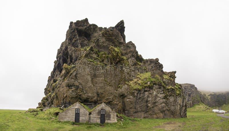Drangurinn-Felsen mit den traditionellen isländischen Häusern, panoramisch lizenzfreie stockbilder