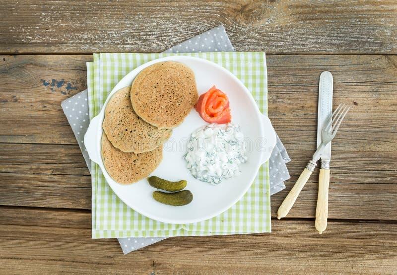 Draniki: crepes de patata con el salmón ahumado, los cornichons y la creatina imágenes de archivo libres de regalías