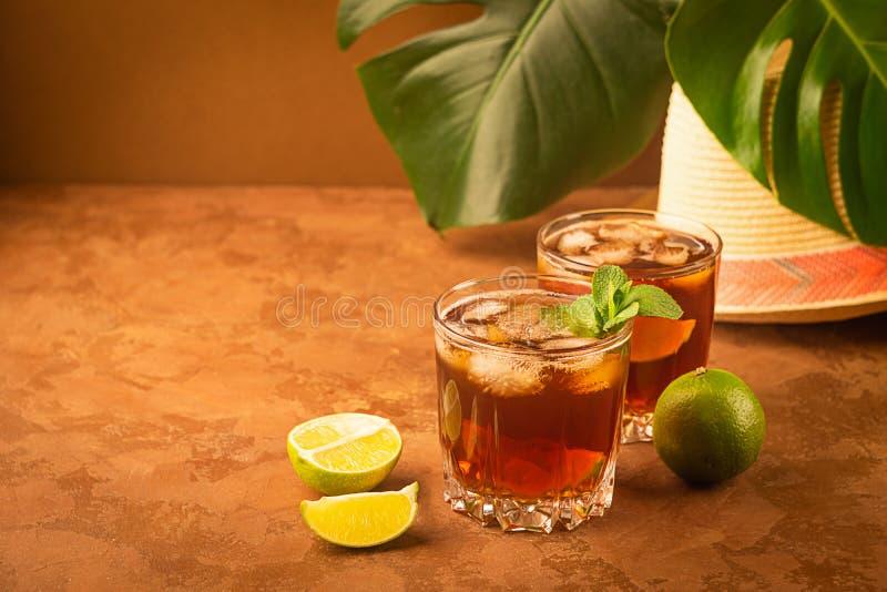 Drank koude thee met ijsblokjes en munt in twee glasdrinkbekers een donkere bruine achtergrond Alcoholische of niet-alkoholische  royalty-vrije stock afbeelding