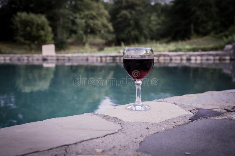 Drank in lang glas in poolside Verfrissing op de zomerdag Purpere sapcocktail of wijnstok Berg bosachtergrond royalty-vrije stock afbeelding