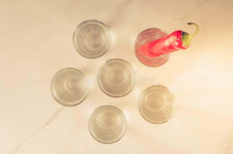 Drank met schoten van wodka en Spaanse peper/Drank wordt geplaatst met schoten van wodka wordt geplaatst en Spaanse peper op een  royalty-vrije stock afbeeldingen