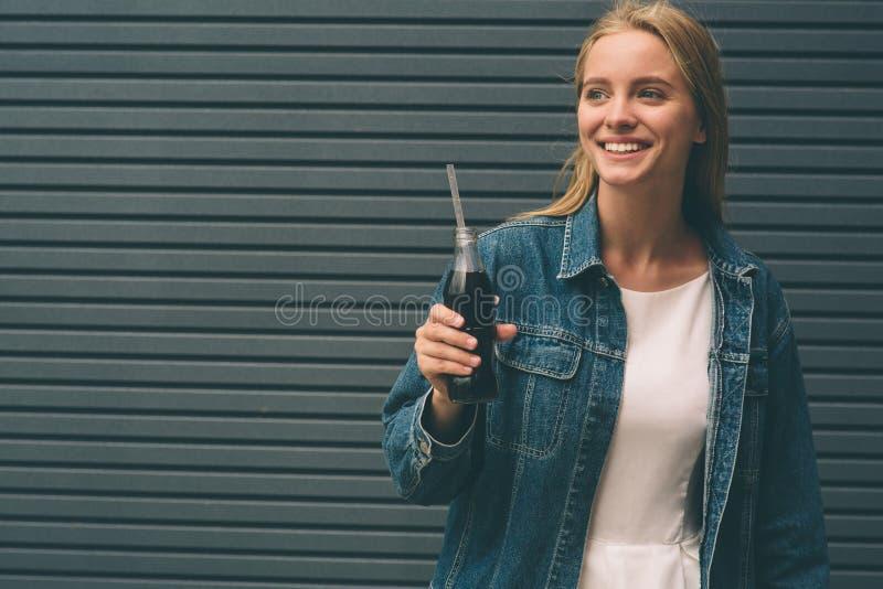 Dranken, mensen en levensstijlconcept - sluit omhoog van het gelukkige vrouw drinken met stro dichtbij de grijze muur royalty-vrije stock foto's