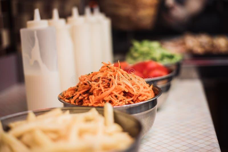 Dranken met tomaten, komkommers, Koreaanse wortelen en frieten, sausschotels op de achtergrond van kebabs en gebraden kippenvlees royalty-vrije stock afbeelding