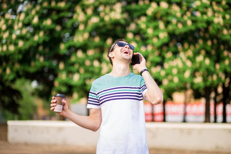 Dranken, technologie en mensenconcept - mens met koffiekop en smartphone bij straat het spreken stock foto's