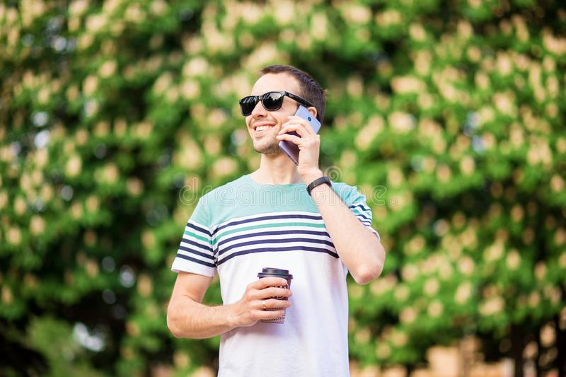 Dranken, technologie en mensenconcept - sluit omhoog van zakenman met koffiekop en smartphone op straat royalty-vrije stock foto