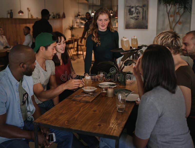 Dranken van serveerster de dienende klanten in een bar bij nacht stock afbeelding