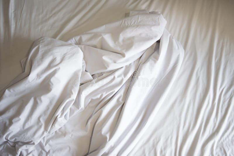 Drap qui n'est pas encore fait du pli et couverture blanche dans la chambre à coucher après sommeil sur le tissu froissé de vue s photo libre de droits