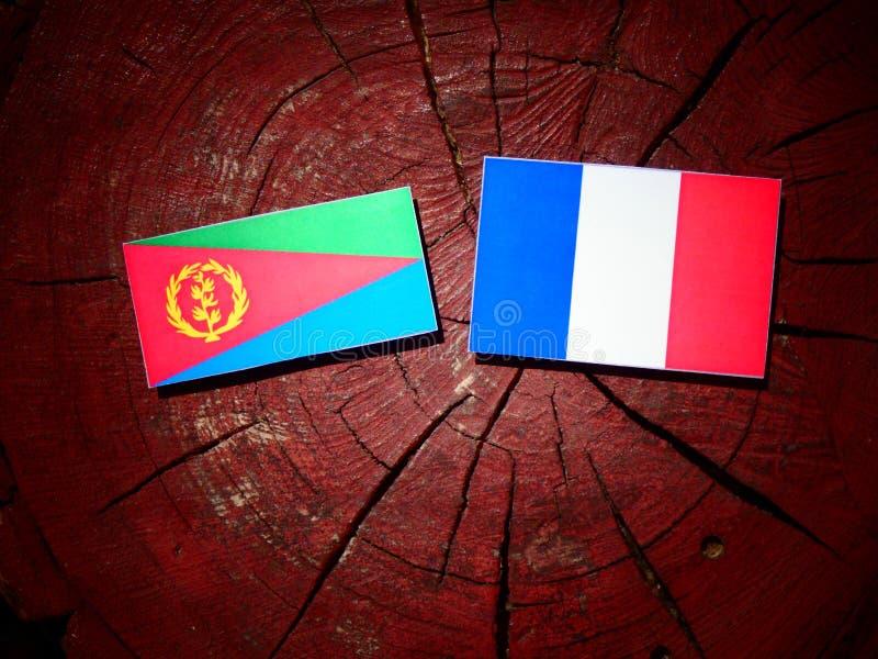 Drapeau érythréen avec le drapeau français sur un tronçon d'arbre d'isolement photographie stock libre de droits