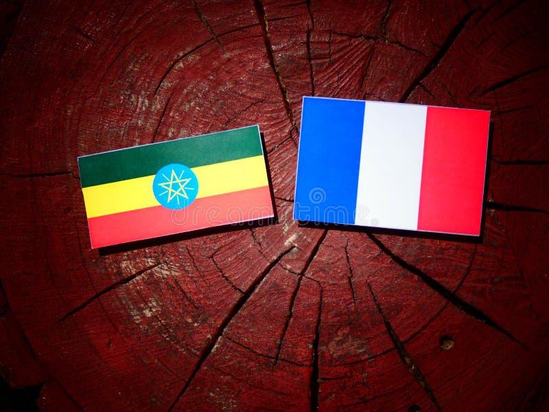 Drapeau éthiopien avec le drapeau français sur un tronçon d'arbre d'isolement photos stock