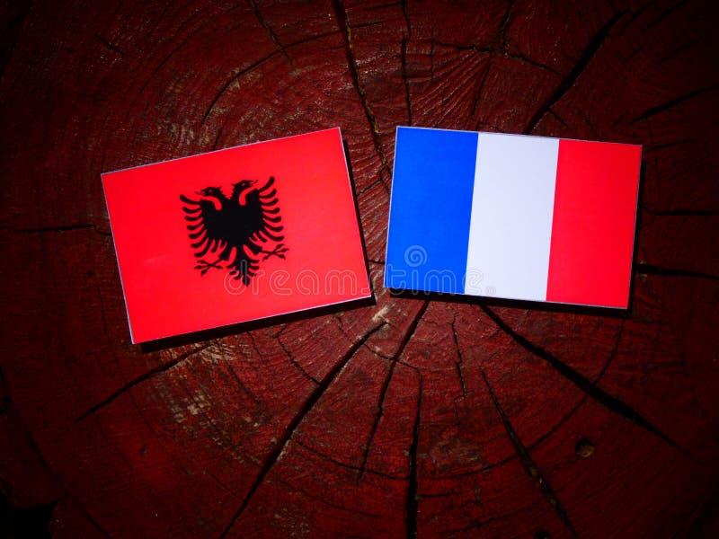 Drapeau albanais avec le drapeau français sur un tronçon d'arbre d'isolement photographie stock