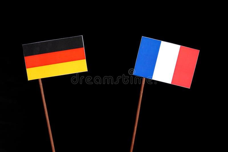 Drapeau allemand avec le drapeau français d'isolement sur le noir images libres de droits