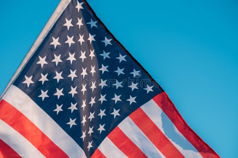 Drapeau américain dans un ciel bleu, fin  Symbole de quatrième de Jour de la Déclaration d'Indépendance de juillet aux Etats-Unis photographie stock