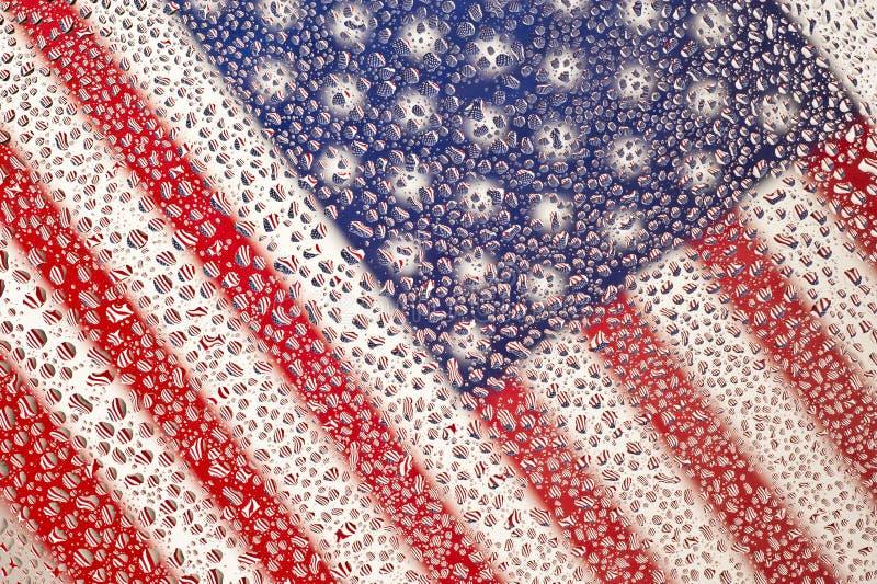 Drapeau américain en gros plan diagonal photographié par la fenêtre humide photo stock