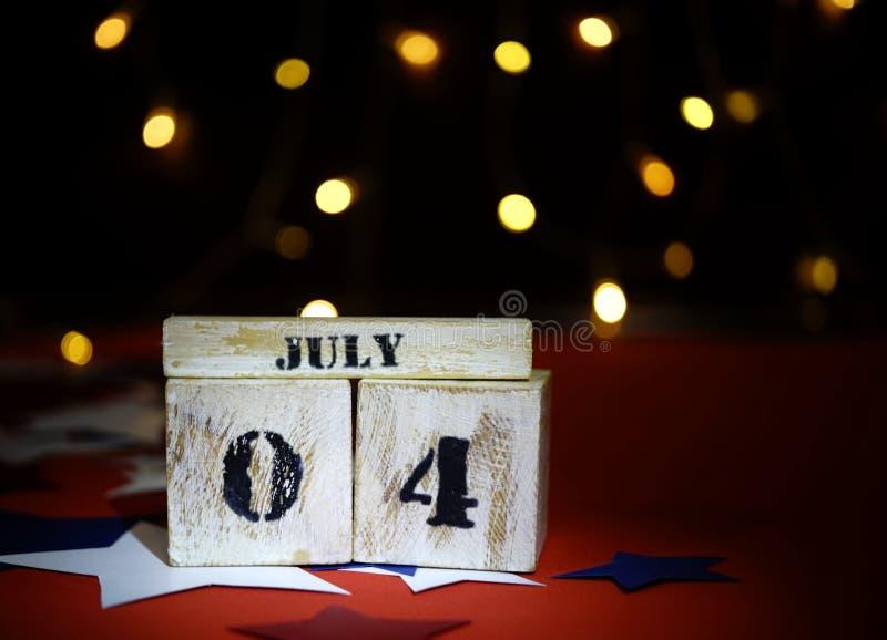 Drapeau américain hérissé et calendrier en bois de cube avec le 4ème juillet, date de Jour de la Déclaration d'Indépendance des E photos stock