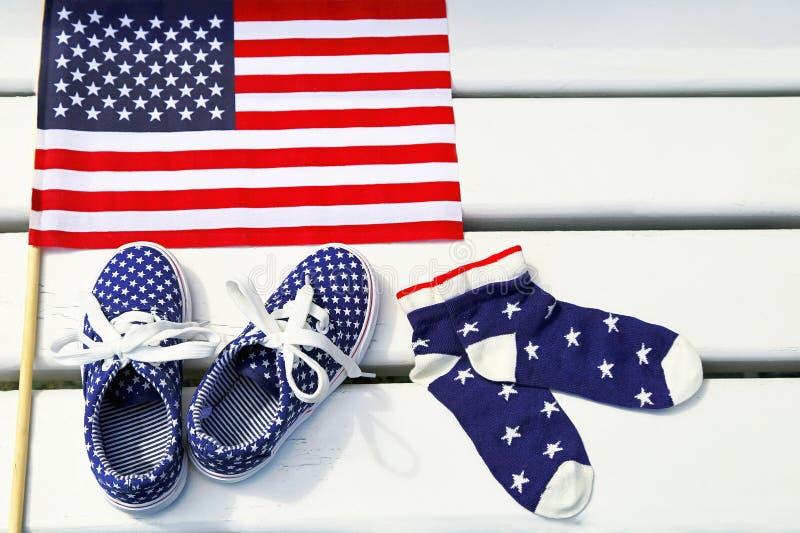 Drapeau américain, les espadrilles des enfants, chaussettes sur le fond en bois blanc photo libre de droits
