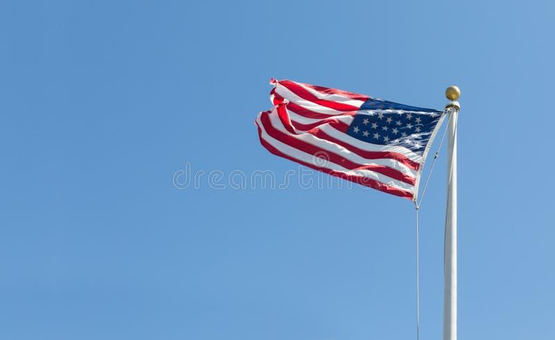 Drapeau américain sur le fond de ciel bleu, tourné vers la gauche photo stock