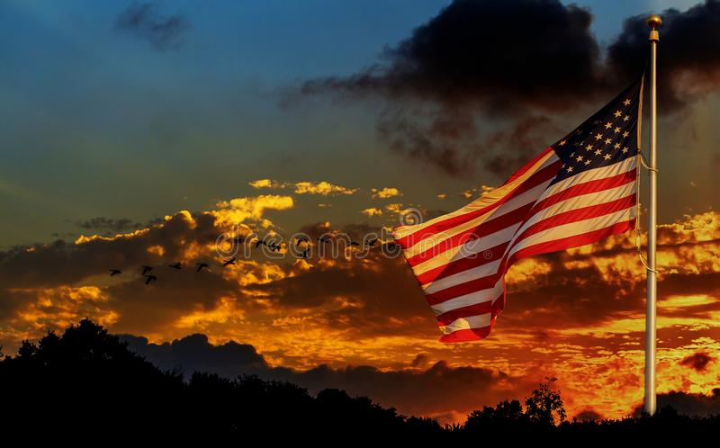 Drapeau américain sur le mât de drapeau ondulant dans le drapeau américain de vent devant le ciel lumineux photo stock