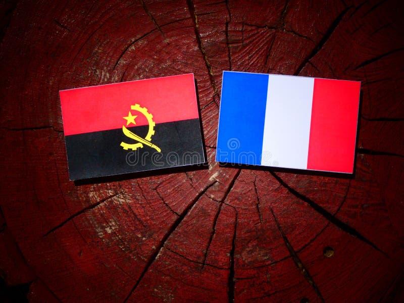 Drapeau angolais avec le drapeau français sur un tronçon d'arbre d'isolement images libres de droits