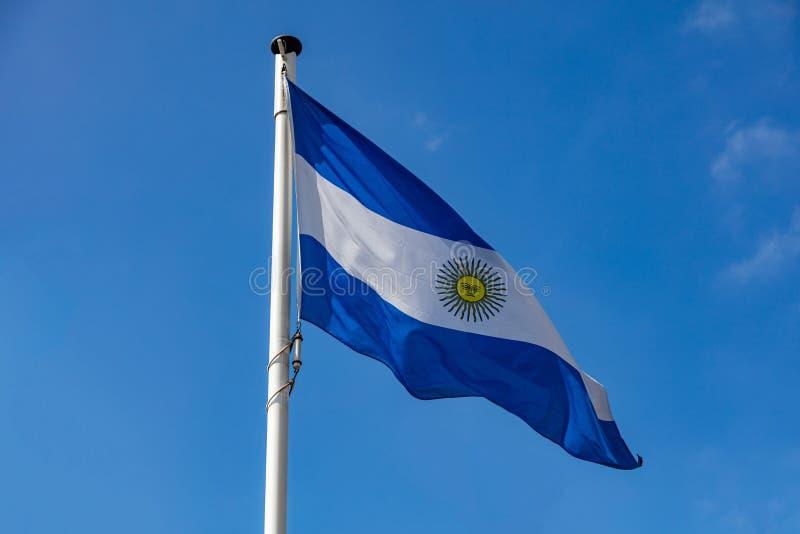Drapeau argentin ondulant contre le ciel bleu clair photos stock