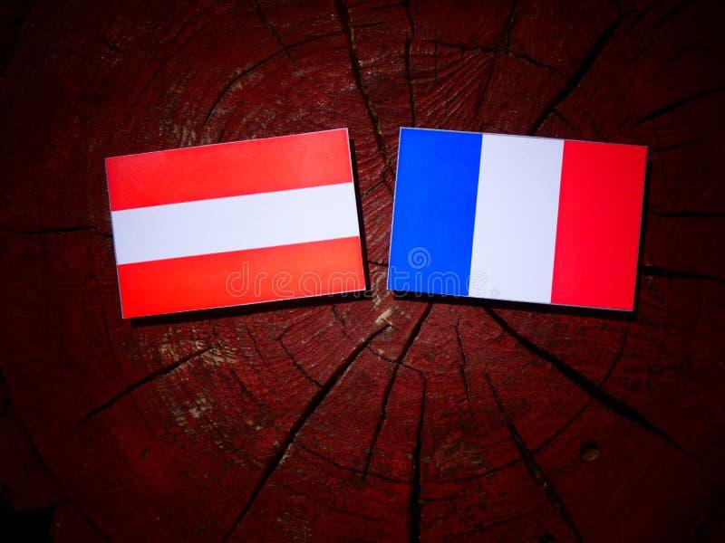 Drapeau autrichien avec le drapeau français sur un tronçon d'arbre d'isolement image stock