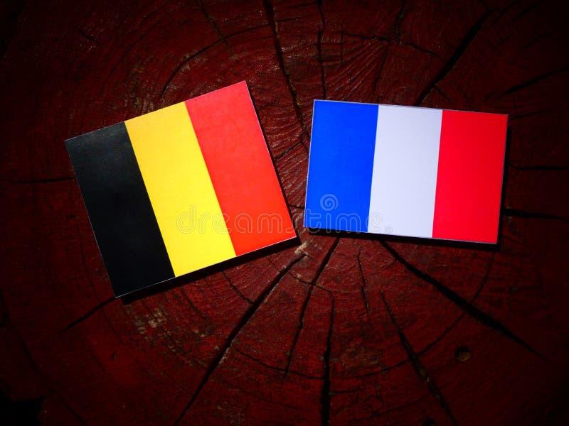 Drapeau belge avec le drapeau français sur un tronçon d'arbre d'isolement photo libre de droits