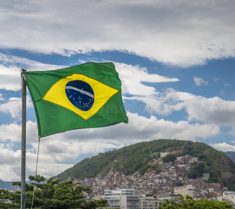 Drapeau brésilien ondulant avec un favela à l'arrière-plan photographie stock