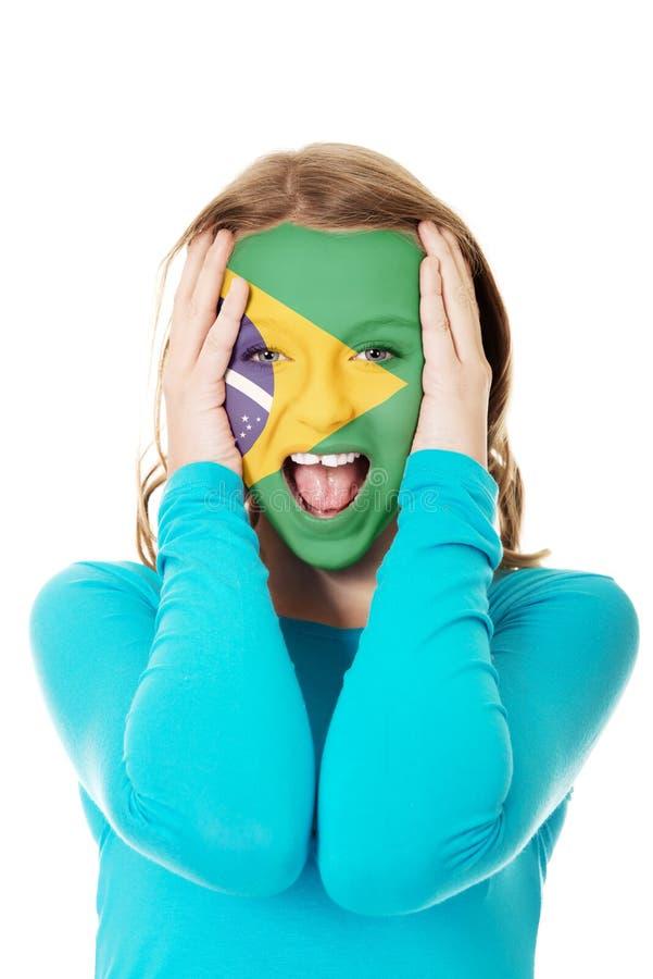 Drapeau brésilien peint sur le visage de la femme photos stock