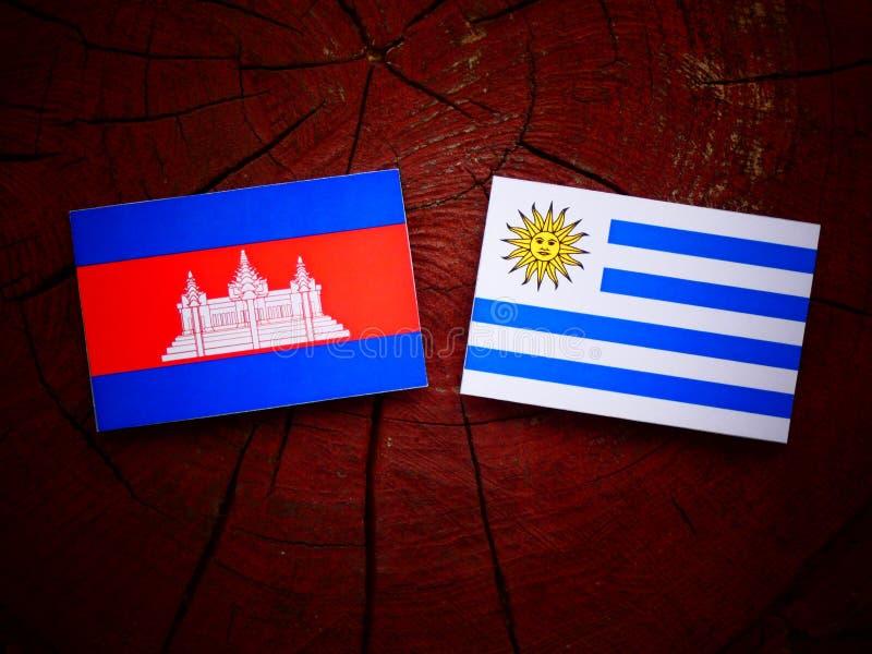 Drapeau cambodgien avec le drapeau d'Uruguaian sur un tronçon d'arbre d'isolement illustration stock