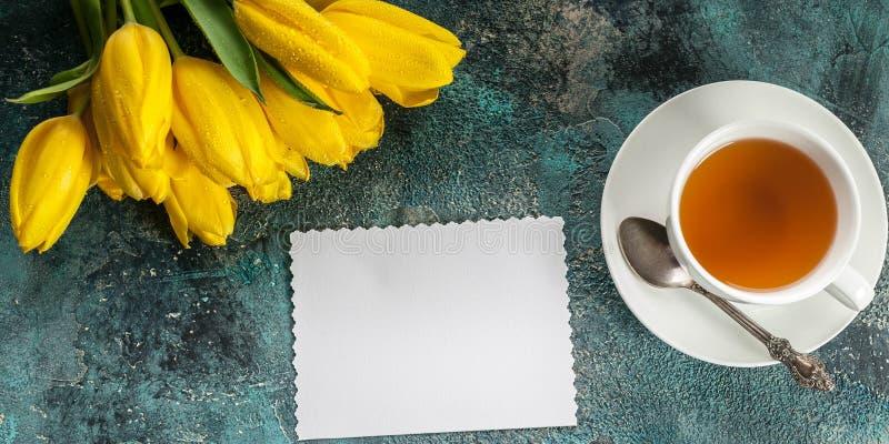 drapeau Carte vierge blanche, tulipes jaunes, tasse de thé sur le fond concret bleu Vue supérieure photographie stock libre de droits